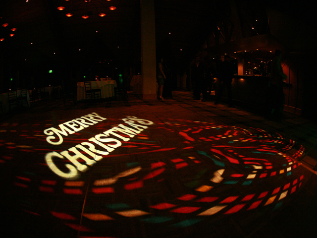 Christmas monogram projected onto the floor at an event